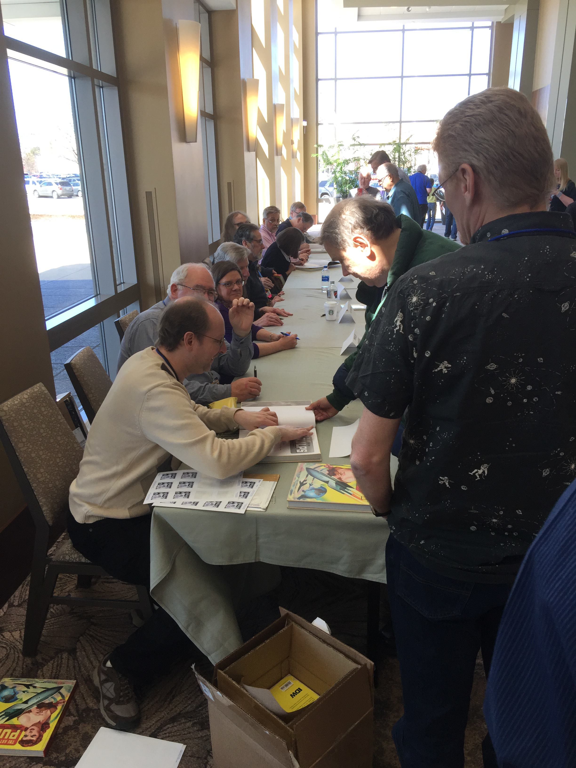 Book signing, with all the contributors lined up to sign copies